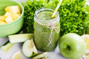 Fresh organic green smoothie with salad apple cucumber pineapple and lemon as healthy drink
