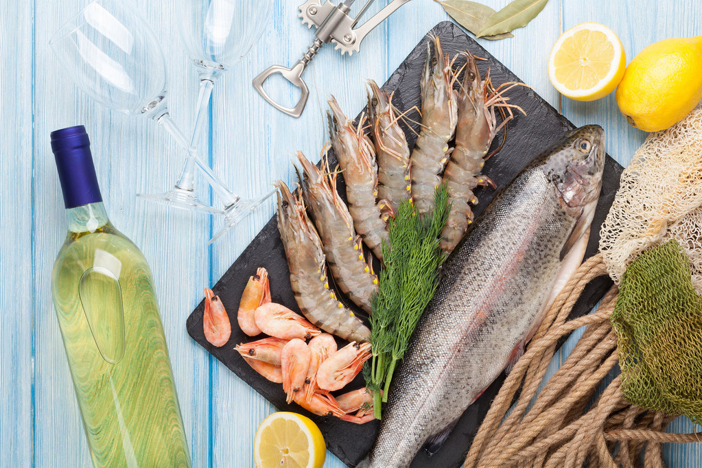 Fresh raw sea food with spices and whtie wine bottle on wooden table background. Top view