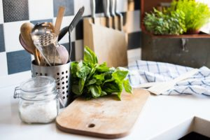 A bunch of basil on the board on the kitchen table, home kitchen supplies for cooking.