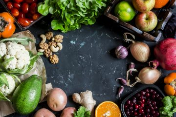 Healthy food background. Assortment of fresh vegetables and fruits on a dark background. Free space for text top view. Flat lay